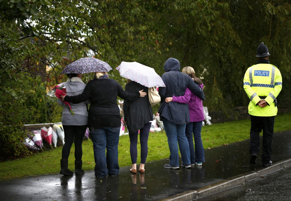 Women embrace before laying floral tributes close to where police constables Fiona Bone and Nicola Hughes were killed in Hattersley (Reuters)