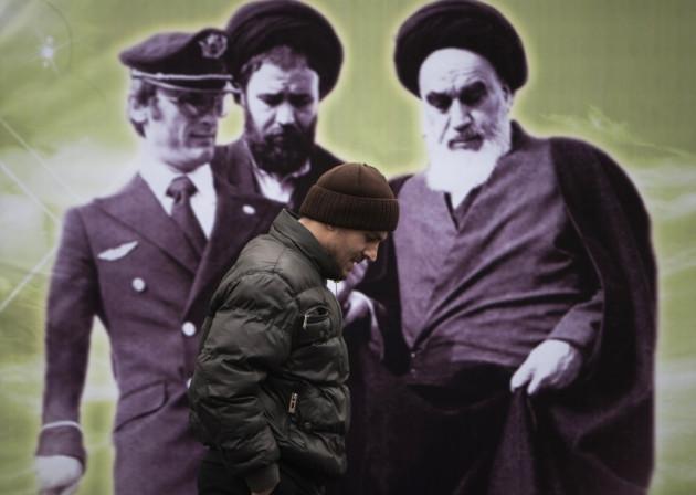 An Iranian man walks past a banner with an image of Iran's late leader Ayatollah Ruhollah Khomeini