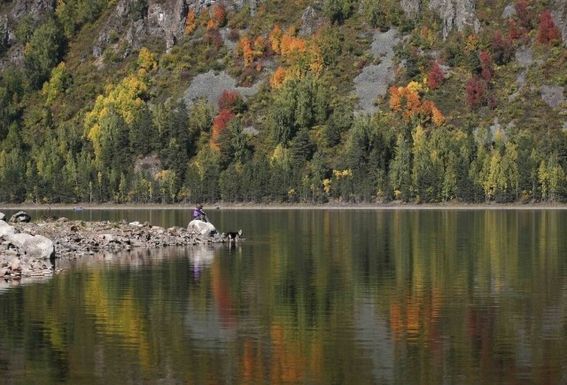 Local residents sit on a bank of the Yenisei River surrounded by reflection of the Siberian taiga in autumn foliage south of the city of Krasnoyarsk, September 13, 2012.  The first day of autumn arrived across the northern hemisphere with autumnal equinox