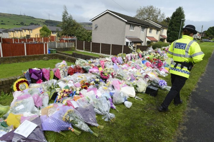 An officer stands by floral tributes near the scene where two female police officers were shot, in Hattersley near Manchester