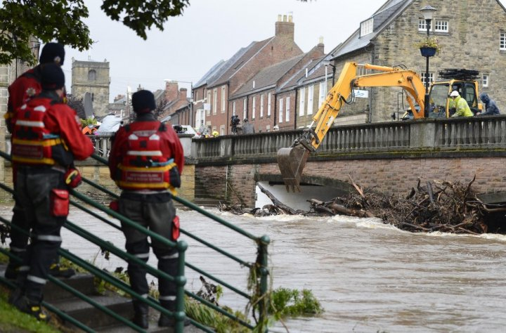 Debris is cleared from a bridge following flooding in Morpeth (Reuters)