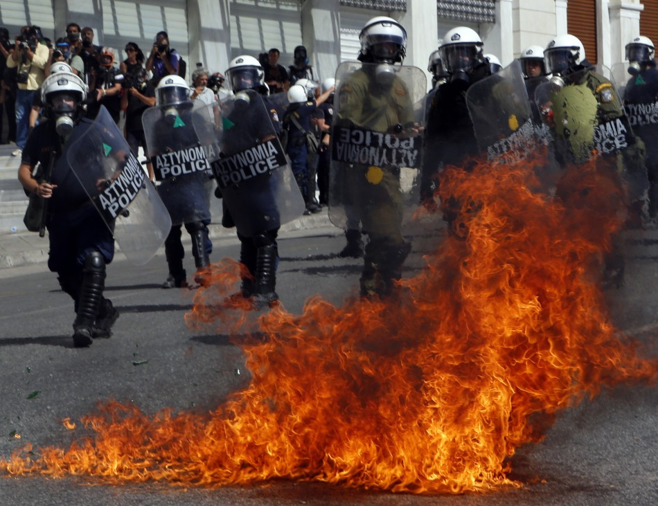 A molotov cocktail explodes beside riot police officers near Syntagma square during a 24-hour labour strike in Athens