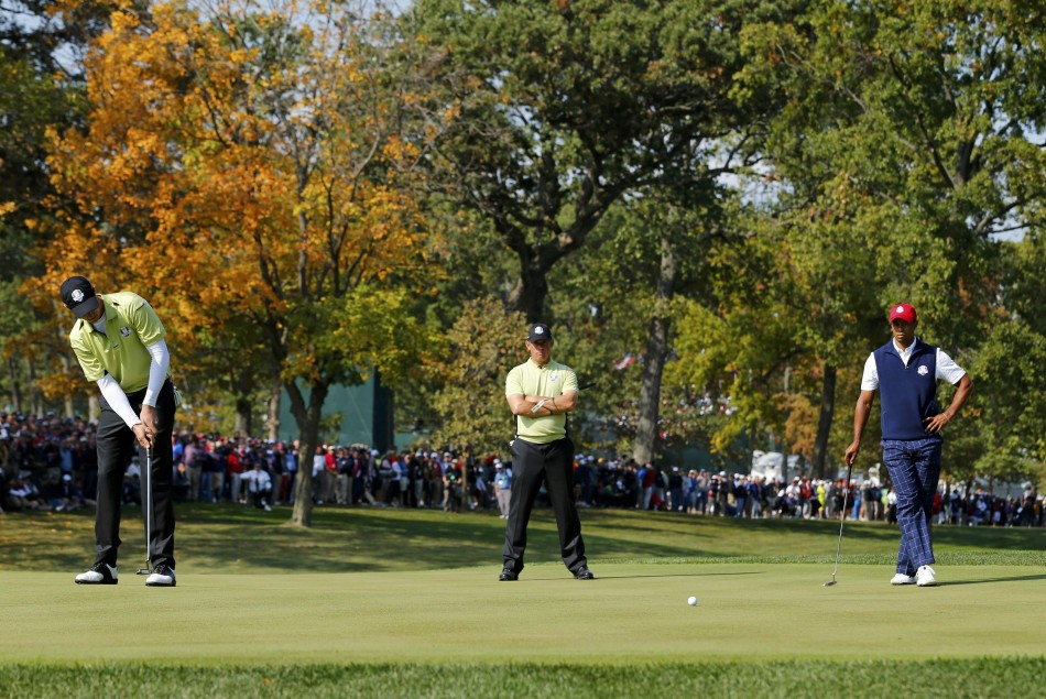Team Europe's Colsaerts sinks a par putt in front of team-mate Westwood and Team USA's Woods