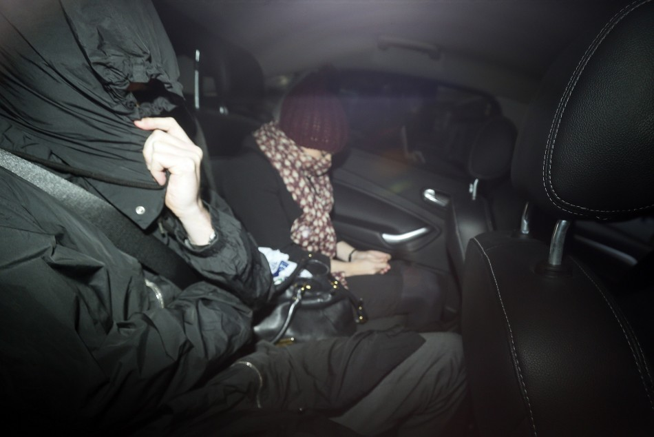 Former UBS trader John Hughes covers his face as he is driven from Southwark Crown Court in London