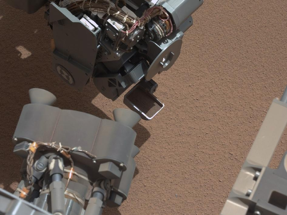 View of Curiosity's first scoop; In the foreground, near the bottom of the image, a bright object is visible on the ground. (Photo: NASA/JPL-Caltech/MSSS)