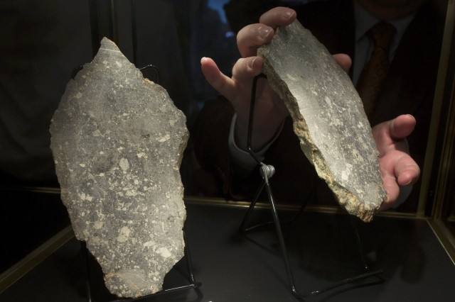 David Herskowitz, a Natural History Consultant at Heritage Auctions, handles a portion of Dar Al Gani 1058, the fourth largest piece of moon rock available to the public in New York October 12, 2012. The pieces of the rock, which are one rock split in two