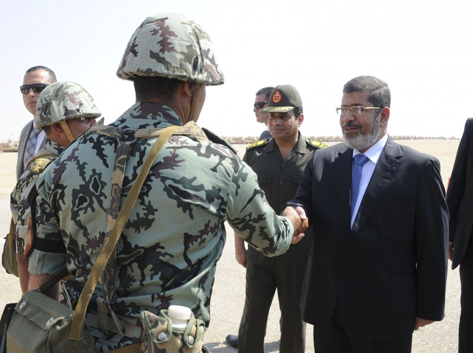 Egypt's President Mursi and Defence Minister Sisi greet soldiers