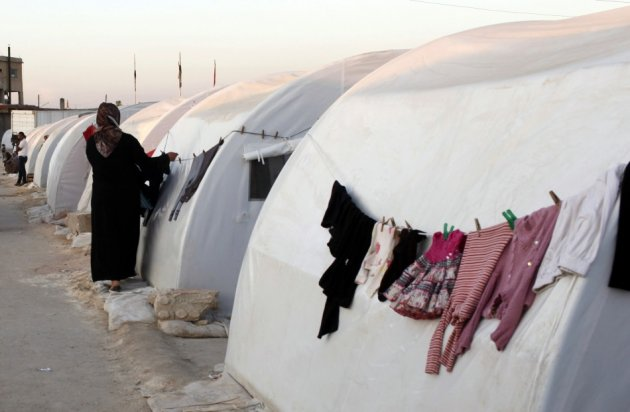 A Syrian refugee hangs her washings on a tent at a refugee camp on the outskirts of Azaz town