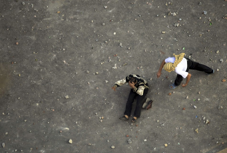 An anti-Muslim Brotherhood demonstrator prepares to throw stones as another falls on the ground injured during clashes
