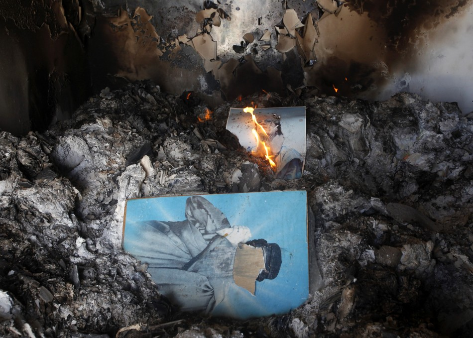 People burn pictures of Libyan leader Gaddafi inside the main prison of Gaddafi's forces in Benghazi