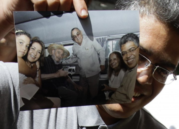 Venezuela's former vice president Elias Jaua shows a picture of himself and former Cuban leader Fidel Castro in Havana