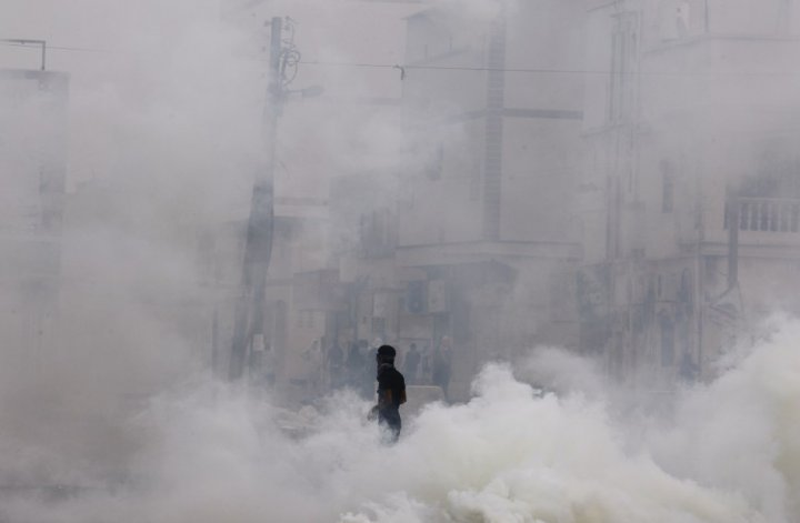 An anti-government protester walks through tear gas during clashes with riot police in the village of Mameer