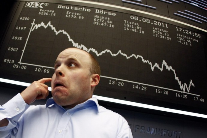 A trader reacts in front of the DAX index board at Frankfurt's stock exchange