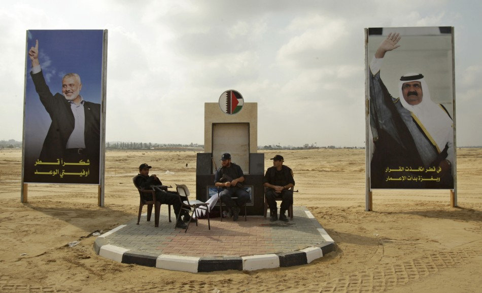 Members of Hamas security forces sit between posters depicting senior Hamas leader Haniyeh and Qatar's Emir Sheik Hamad