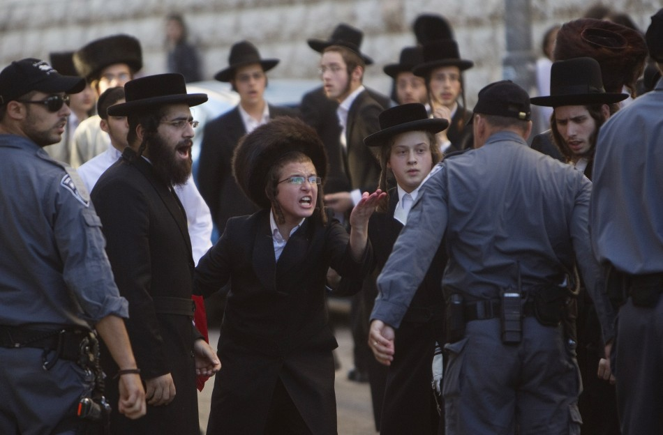 Ultra-Orthodox Jews shout at a policeman during a protest against the opening of a road on the Sabbath