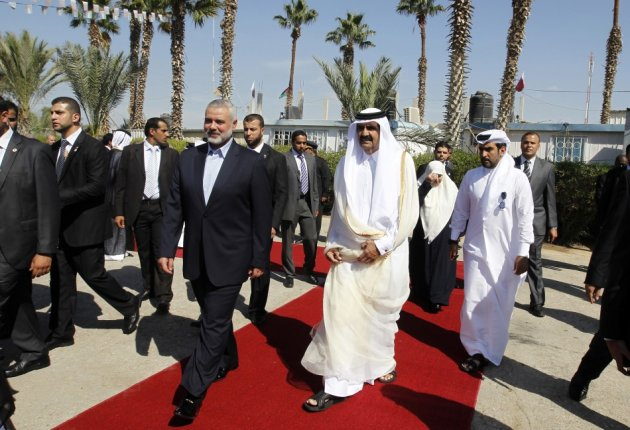 Hamas Prime Minister Haniyeh walks with the Emir of Qatar in Rafah