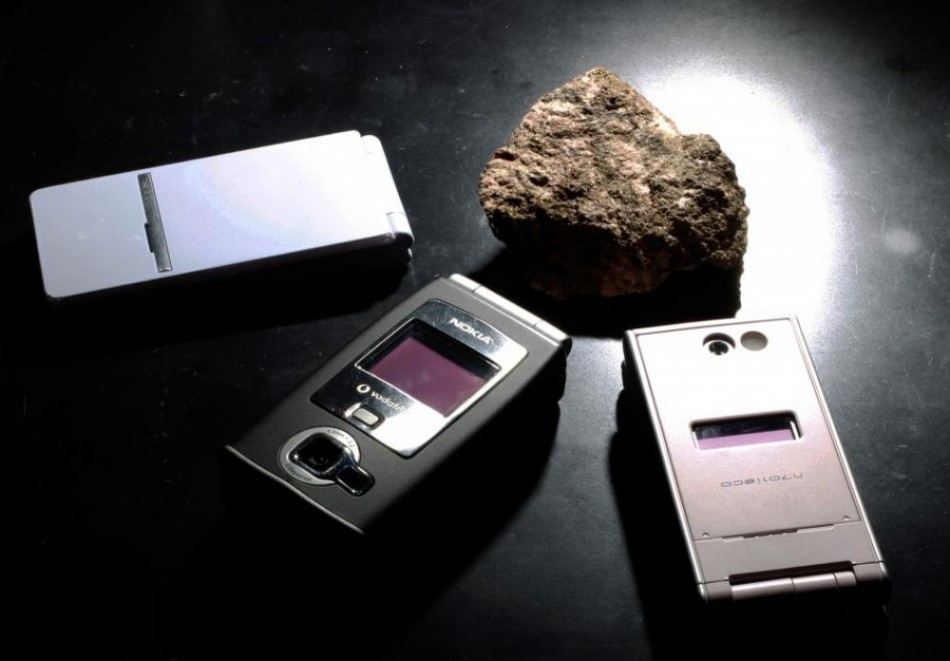 A bastnaesite mineral containing rare earth is pictured next to cell phones, which utilises the minerals during manufacturing at a laboratory (PHOTO: REUTERS)