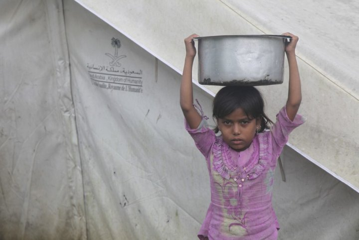 A girl balances a pot on her head at a camp for internally displaced persons in Myanmar's Rakhine state