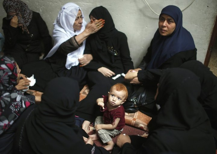 The daughter of a Hamas gunman sits near her crying mother during funeral in northern Gaza
