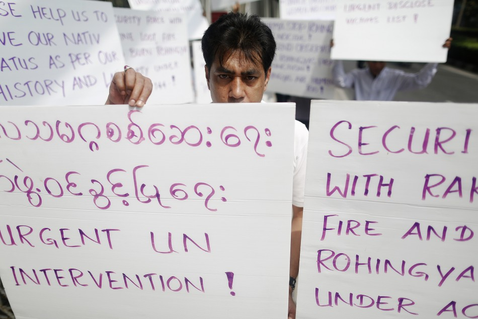 Men hold banners as they protest in front of the U.S. embassy in Bangkok
