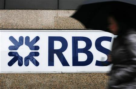 A woman walks past the Royal Bank of Scotland's offices in the City of London