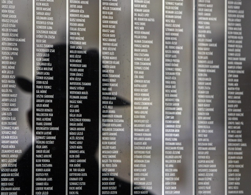 Hungarian man is reflected on a wall containing the names of victims at Budapest's Holocaust Memorial Centre