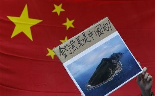 A protester holds a photo of the disputed Senkaku or Diaoyu islands (Photo: Reuters)