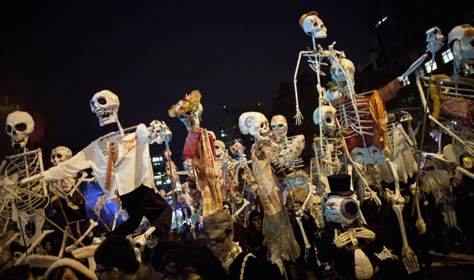 People hold up life-sized skeleton puppets while walking in the 39th Annual Halloween Parade in New York