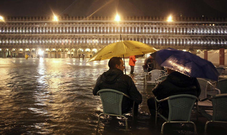 People walk in a flooded street during a period of seasonal high water in Venice