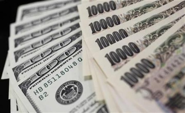 A picture illustration shows U.S. 100 dollar bank notes and Japanese 10,000 yen notes taken in Tokyo
