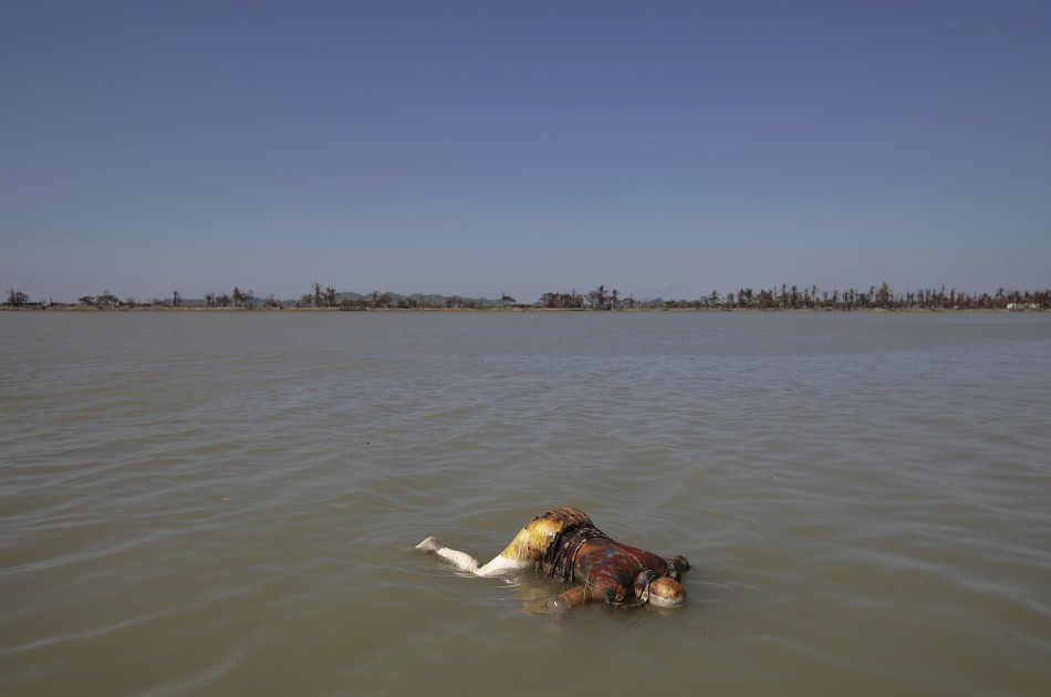 A dead body floats in the sea near the part of Pauktaw township that was burned in recent violence