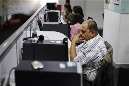 Office workers sit in front of their workstations on the floor of an outsourcing centre in Bangalore, February 29, 2012.