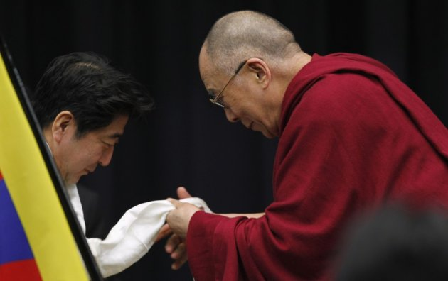 Tibetan spiritual leader the Dalai Lama gives a Tibetan shawl to Japan's main opposition Liberal Democratic Party president Shinzo Abe, at the upper house members' office building in Tokyo