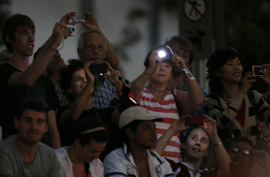 Tourists take photographs of a cloudy sky during a full solar eclipse in the northern Australian city of Cairns
