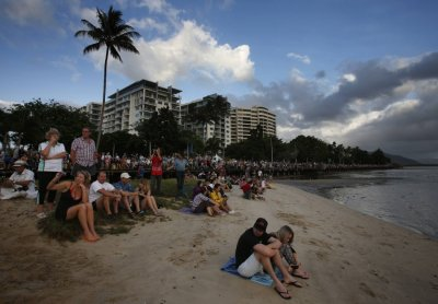 Tourists look at a cloudy sky as a full solar eclipse begins in the northern Australian city of Cairns