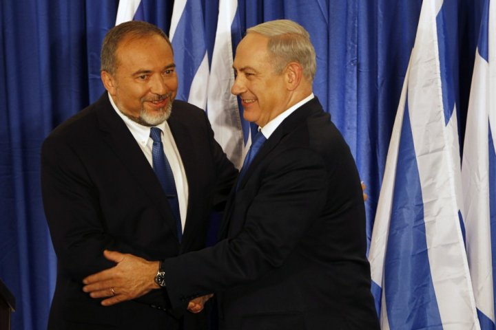 Benjamin Netanyahu and Avigdor Lieberman shake hands at a joint news conference in Jerusalem