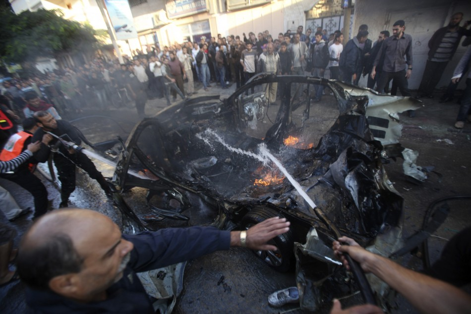 Palestinians extinguish the fire after an Israeli air strike on a car in Gaza City