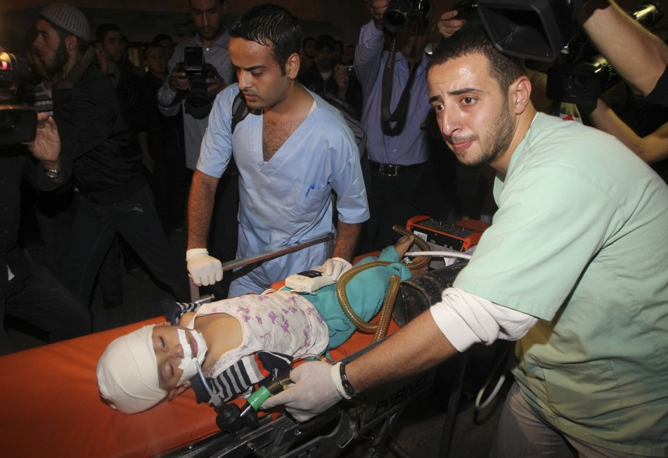 Palestinians wheel a wounded child into a hospital after an Israeli air strike in Gaza City