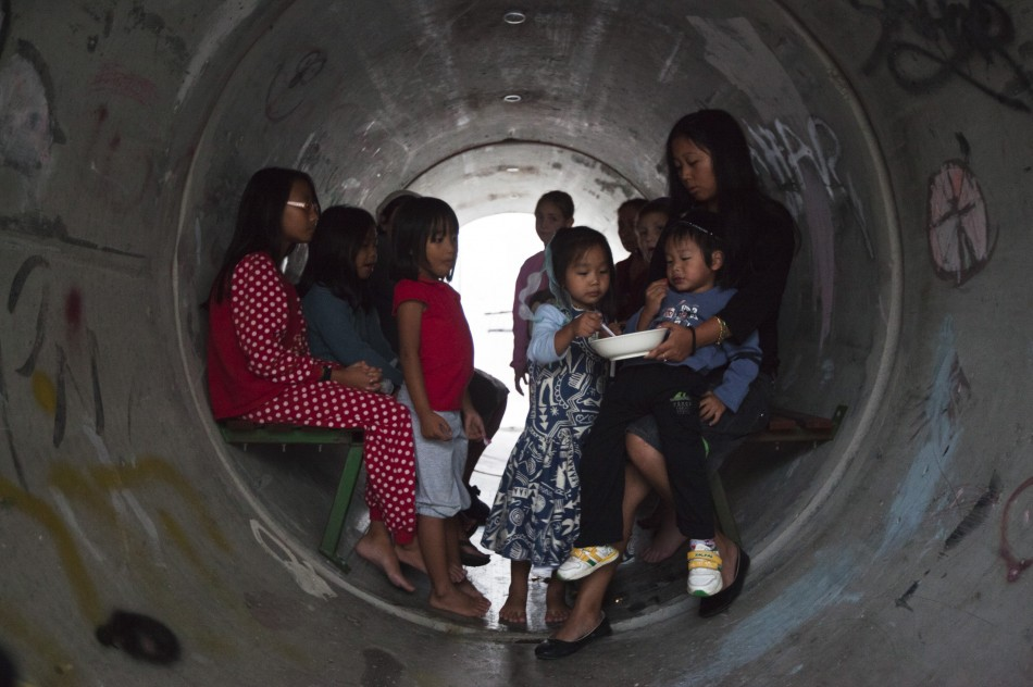 Israelis sit inside a sewage pipe used as shelter during an alert warning of incoming rockets