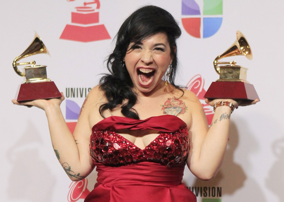 Carla Morrison poses backstage with the awards for best alternative album and best alternative song during the 13th Latin Grammy Awards in Las Vegas