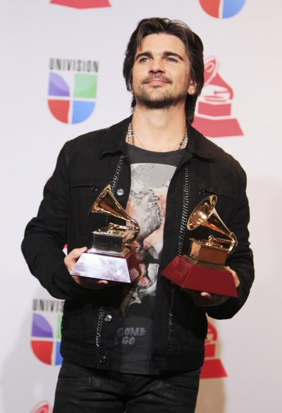 Juanes poses with awards for best long form music video and album of the year for MTV Unplugged during the 13th Latin Grammy Awards in Las Vegas