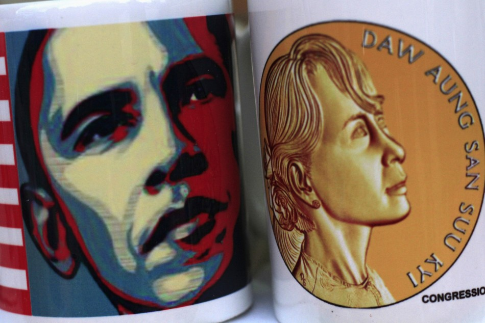 The portrait of U.S. President Obama is seen printed on a cup which is placed next to another with the portrait of Aung Sun Suu Kyi (Reuters)