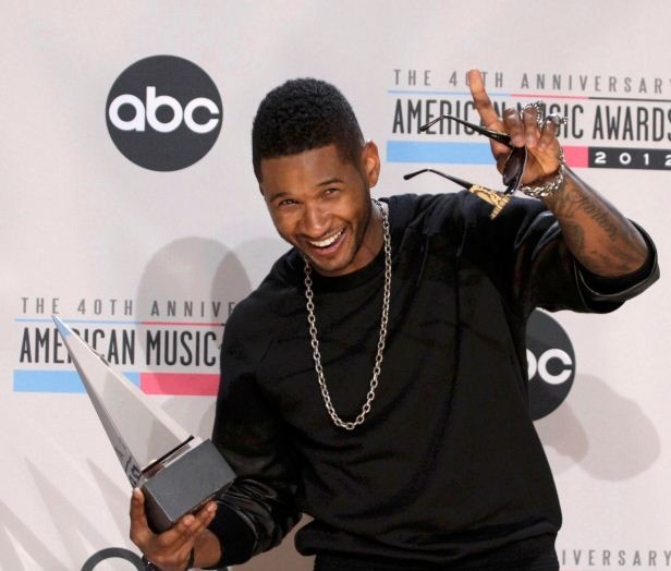 Usher holds up the award for favorite male artist Soul/R&B at the 40th American Music Awards in Los Angeles
