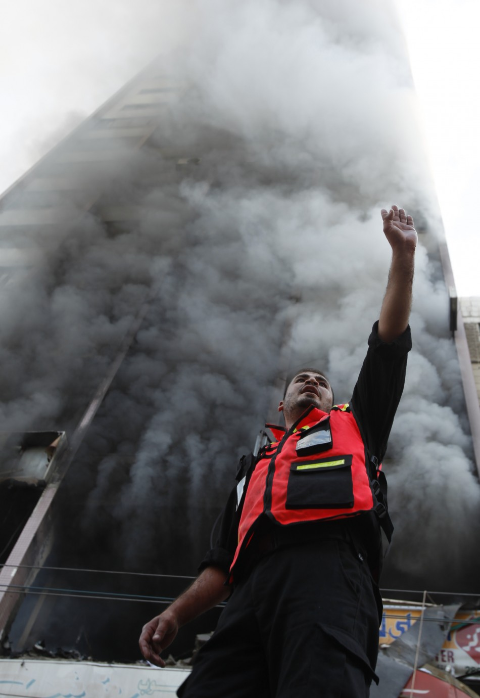 A Palestinian firefighter gestures as smoke rises out of a building that also houses international media offices,