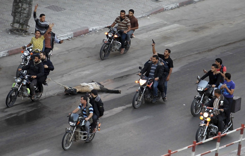 Palestinian gunmen ride motorcycles as they drag the body of a man, who was suspected of working for Israel,