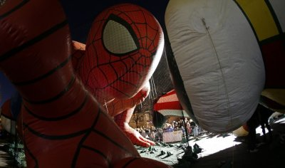 People viewing floats, pass by a balloon in the shape of Spider Man ahead of the Macys Thanksgiving Parade in New York