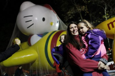 Tania Grove poses for a photo with her daughters Morgan and Abby in front of a Hello Kitty float ahead of the Macys Thanksgiving Parade in New York