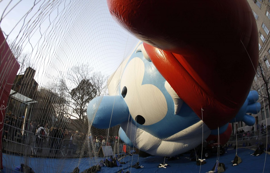 Balloon in the shape of Papa Smurf is held down by netting as it gets inflated with helium ahead of the Macys Thanksgiving Parade in New York