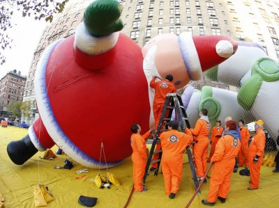Workers fill the beard of a balloon in the shape of Santa Claus, with helium, ahead of the Macys Thanksgiving Parade in New York