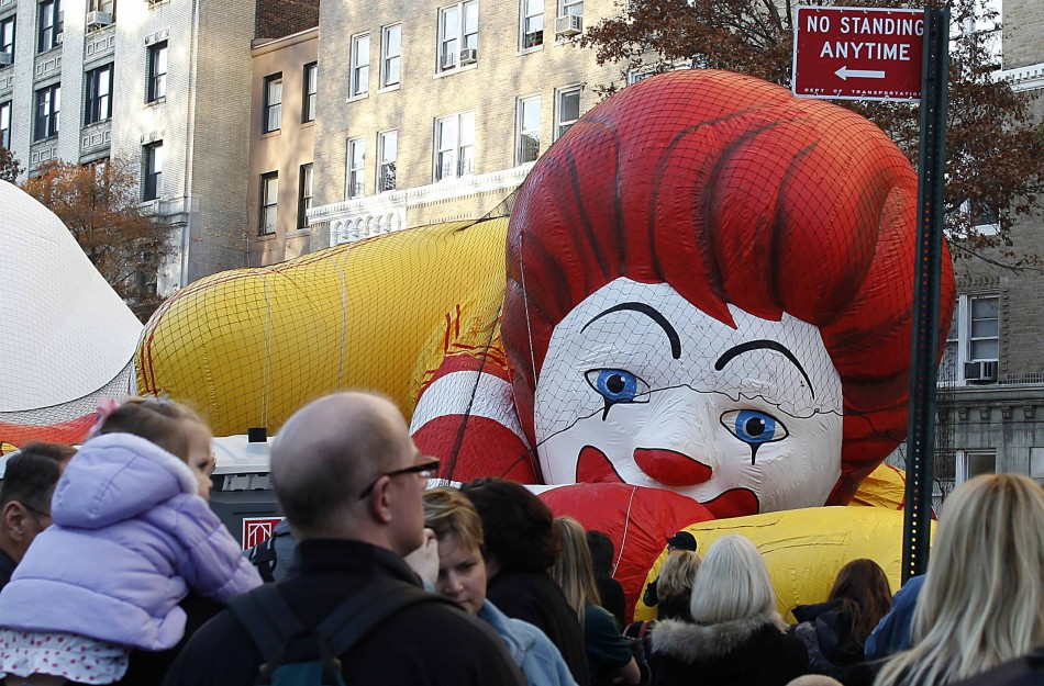 Workers fill a balloon in the shape of Ronald McDonald, with helium, ahead of the Macys Thanksgiving Parade in New York